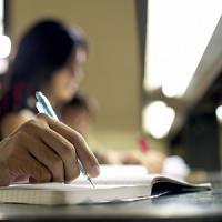 Primo piano di una mano che scrive su di un blocco di appunti. Sullo sfondo un'aula studio.